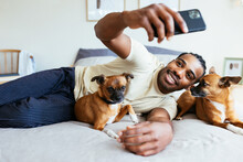 Happy Owner Taking Selfie With Dogs On Bed