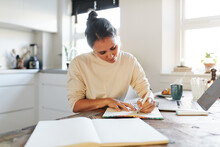 Woman Sketching A Design In A Book
