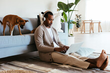Barefoot Black Man Using Laptop Near Couch And Dog