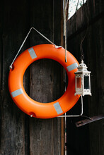 Orange Life Buoy Hanging On A Wooden Wall