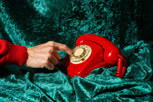 Man Dialing On A Red Telephone