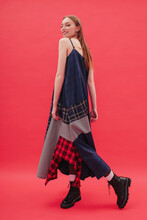 Model Posing In Plaid Dress By Red Background