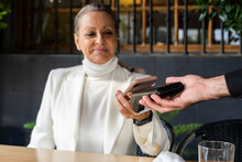 Senior Business Woman Paying With Mobile Phone At Restaurant