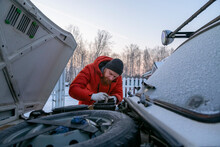 Focused Man Repairing Car Engine Details In Wintertime