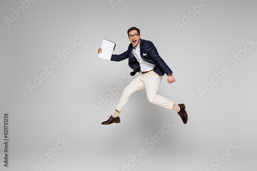 Obraz full length of young businessman holding paper folder while flying on grey - fototapety do salonu