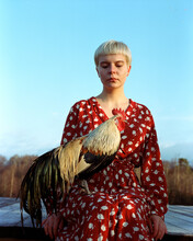 Girl Sitting With The Rooster