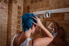 Androgyne Woman Dyeing Her Hair Blue With The Hands At Home