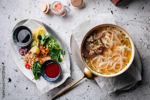 Fototapeta Top view on vietnamese traditional soup pho bo with sauces and toppings obraz