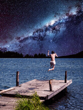 Surrealistic Collage.Man Dives Into The Water Off The Pier On The Background Of The Milky Way