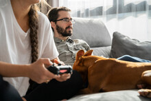 Young Couple Relaxing Andplaying With Pets At Home In Living Room