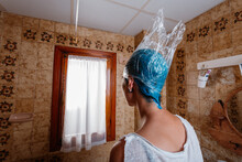 Woman Waiting For The Blue Hair Dye To Be Ready To Wash