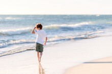 Boy Walking Along A Beach On A Sunny Afternoon