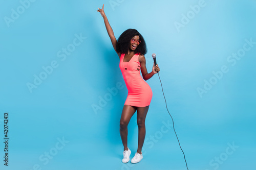 Obraz Photo of lady hold mic sing look empty space raise hand wear sunglass mini dress shoes isolated blue color background - fototapety do salonu