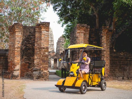 Fototapeta Woman wearing purple dress on electric car and old temple at Sukhothai, Thailand