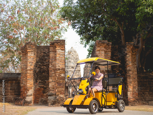 Fotografie, Obraz Woman wearing purple dress on electric car and old temple at Sukhothai, Thailand