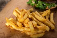Patatine Fritte Su Un Tavolo Di Legno Vicino Ad Un Hamburger