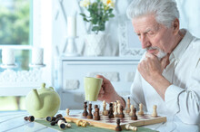 Portrait Of Senior Man Looking At Chess Board While Drinking Tea At Home