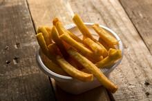 Patatine Fritte Dentro Un Contenitore Di Plastica Su Un Tavolo Di Legno