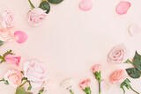Pink roses and carnation flowers on pink background with space for text in the middle