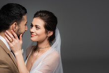 Happy, Elegant Bride Touching Face Of Muslim Fiance Isolated On Grey