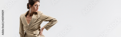Obraz sensual brunette woman looking away while posing with hand on hip isolated on grey, banner - fototapety do salonu