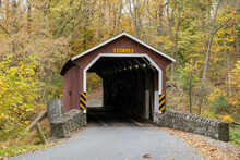 Outdoor View Of The Red Covered Bridge Inside Of The Forest In The Daytime