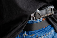 Hided Handgun Under The Denim Belt. A Person Is Hiding A Handgun Under The Denim Belt.