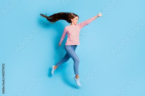 Murais de parede Full length body size photo serious powerful girl jumping imagine flying super w