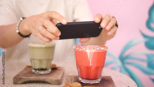 Fototapeta Hands taking a picture of pink smoothie decorated with sprinkles and an Ice coffee served on the wooden trays obraz