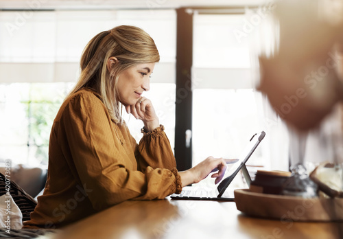 Smiling woman sits at the kitchen table in front of tablet computer and does her Tapéta, Fotótapéta