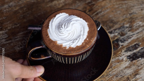 Fototapeta Hand serving a brown mug of plant based hot chocolate with whipped cream on a wooden table obraz