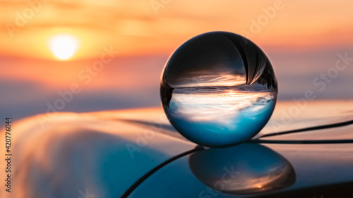 Leinwand Poster Crystal ball sunset shot with reflections on a car roof at Kostenz, Bavarian for