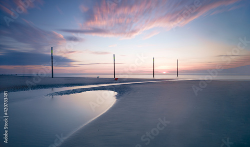 Formation of four tall wooden poles at sandy beach. Sunset sky with colorful clouds.
