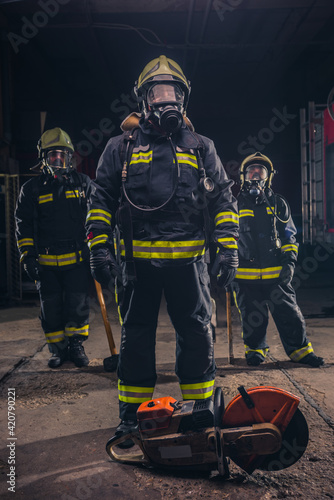 Canvas Print Group of three young fireman posing inside the fire department with uniform and