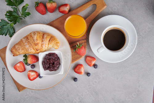 Fototapeta Continental breakfast with assortment of pastries, croissants, Strawberry Jam, coffees and orange juice ,fresh strawberries. obraz