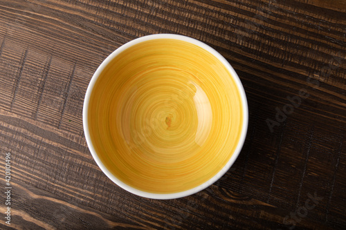 Empty white bowl with hand painted yellow inside Fototapet