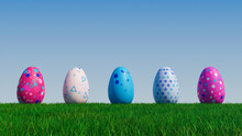 Easter Eggs On A Grass Lawn, With A Clear Blue Sky. Beautiful Pink, And Blue Eggs With Triangle, Floral And Spotted Patterns. 3D Render