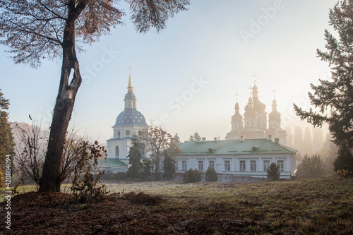 Tablou Canvas Orthodox church in the morning fog at dawn in the middle of the park