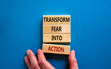 Transform Fear Into Action Symbol. Businessman Holds Wooden Blocks With Words 'Transform Fear Into Action'. Beautiful Blue Background, Copy Space. Business, Transform Fear Into Action Concept.