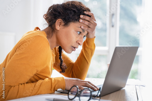 Young woman feeling stressed while looking bank account online Fotobehang