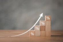 Interest Rate Financial And Mortgage Rates Concept. Wooden Blocks With Icon Percentage Symbol And Arrow Pointing Up. The Economy Is Improving.