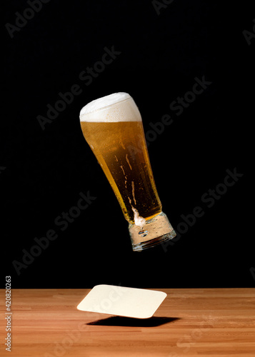 Photo glass of beer isolated on black, falling on a table