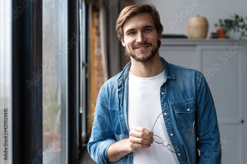 Portrait of smiling young businessman looking at camera in home office.