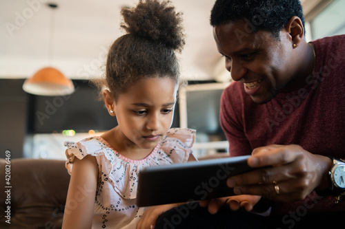 Foto Father and daughter using digital tablet at home.