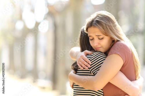 Fotografie, Obraz Regretful woman embracing a friend in the street