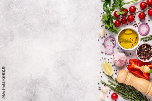 Fototapeta Herbs and condiments on light stone background. obraz