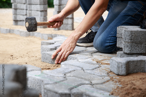 Obraz Hand of professional paver worker lays paving stones in layers for pathway - fototapety do salonu