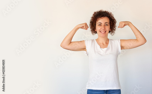 Billede på lærred Beautiful young woman showing biceps expressing strength and fitness concept, he