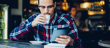 Businessman In Stylish Eyeglasses Drinking Tasty Americano Coffee Reading Web News On Digital Tablet During Free Time In Cafeteria Interior, Young Caucaisan Man Watching Video During Break In Cafe