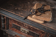 Old Vintage Keys On An Old Battered Book, Antique Wooden Background. The Concept Of Mystery And Discovery, Answers To Questions, A Clue.